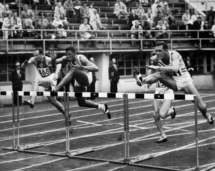 File- This July 26, 1952 file photo shows Milt Campbell, center, of Plainfield, N.J. getting set to clear the final hurdle to make him the winner in the fifth heat of the 110-meter hurdles event in the Olympic decathlon at Helsinki, Finland. Campbell, who became the first black to win the Olympic decathlon in 1956 and went on to play professional football and become a motivational speaker, died Friday Nov. 2, 2012 after a battle with prostate cancer. He was 78. (AP Photo/File)