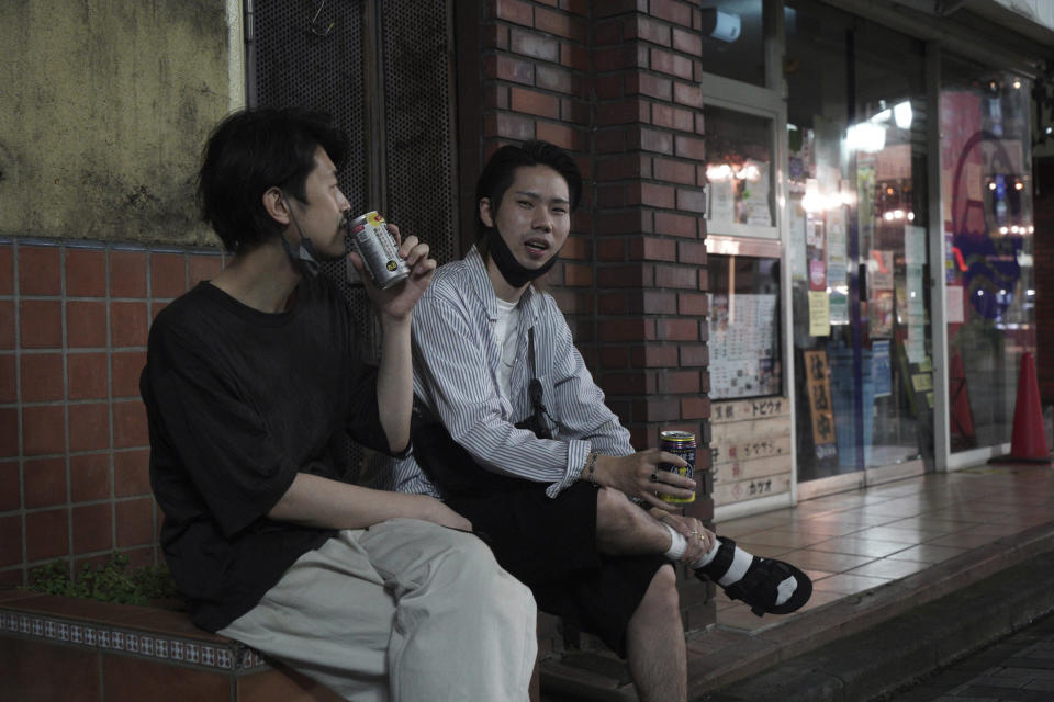"""Naoto Suga, right, 25, drinks canned alcohol roadside with his friend in Tokyo's Shinjuku district Monday, July 19, 2021. """"I don't think the Olympics itself made this (situation), but even before the Games, things like the state of emergency have remained half measures, and I think that's making things worse,"""" Suga said. """"People are all used to the state of emergency, so it's getting less meaningful now."""" (AP Photo/Kantaro Komiya)"""