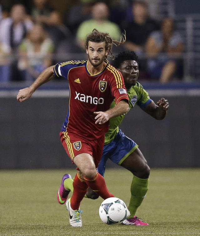 Real Salt Lake's Kyle Beckerman, front, dribbles the ball away from the defense of Seattle Sounders' Obafemi Martins in the first half of an MLS soccer match, Friday, Sept. 13, 2013, in Seattle. (AP Photo/Ted S. Warren)