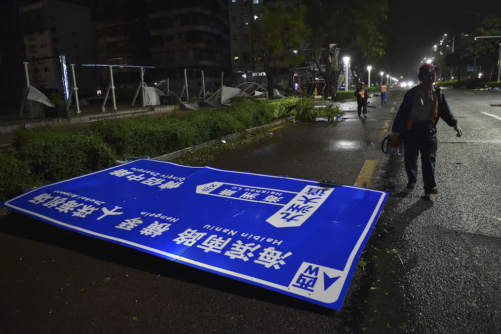 <p>A worker walks by a road sign damaged by Typhoon Mangkhut on a street in Zhuhai, south China's Guangdong Province (Picture: AP) </p>