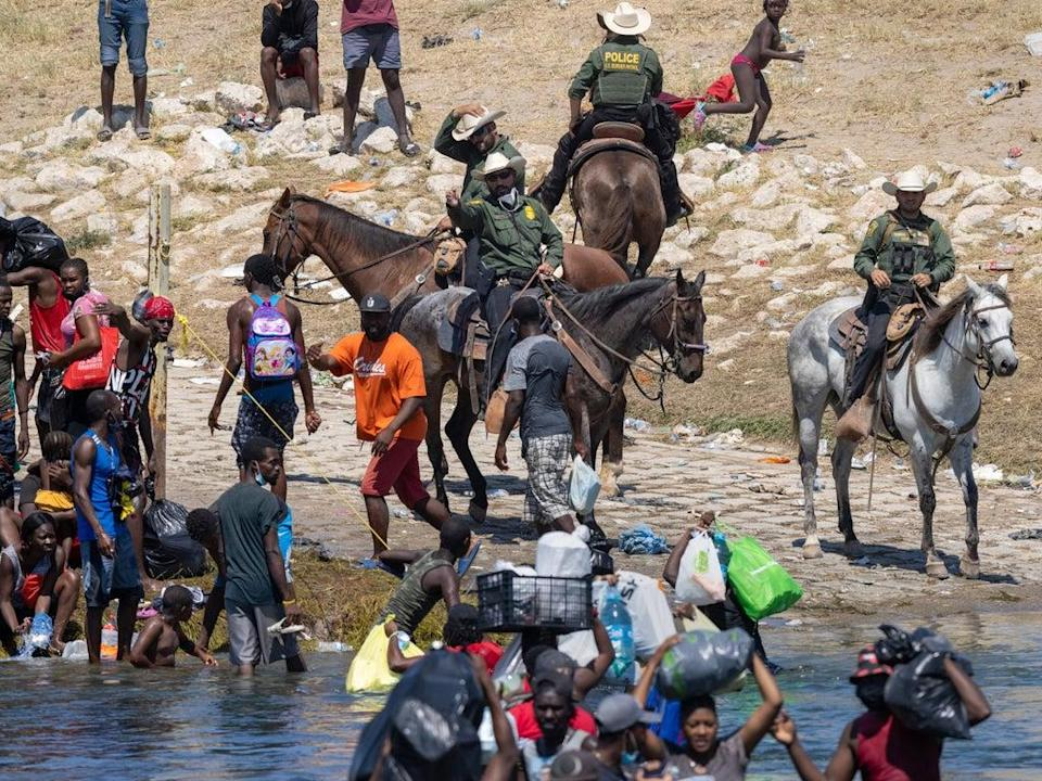 Migrants interact with Border Patrol agents (Getty Images)