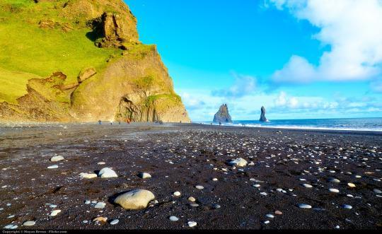 """<p>Another spot we wouldn't recommend for sun bathing – but would absolutely insist you visit to appreciate the wonders of Earth – is this beach on the southern coast of Iceland. Here, the rare black sand leads to two towering basal sea stacks called Reynisdrangar. Their Goonies-eqsue eeriness is only compounded by the folklore of their formation: The stacks are allegedly two trolls who attempted to drag a ship ashore and were frozen by the daylight. <i>(Photo: <a href=""""https://www.flickr.com/photos/aigle_dore/21882243128/"""" rel=""""nofollow noopener"""" target=""""_blank"""" data-ylk=""""slk:Moyan Brenn"""" class=""""link rapid-noclick-resp"""">Moyan Brenn</a>/Flickr)</i><br></p>"""