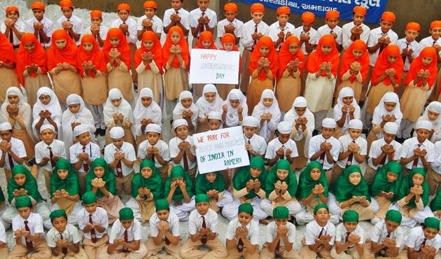 School children dressed in tri-colours of India's national flag, offer prayers on the eve of the country's Independence Day celebrations in the western Indian city of Ahmedabad August 14, 2012. REUTERS/Amit Dave