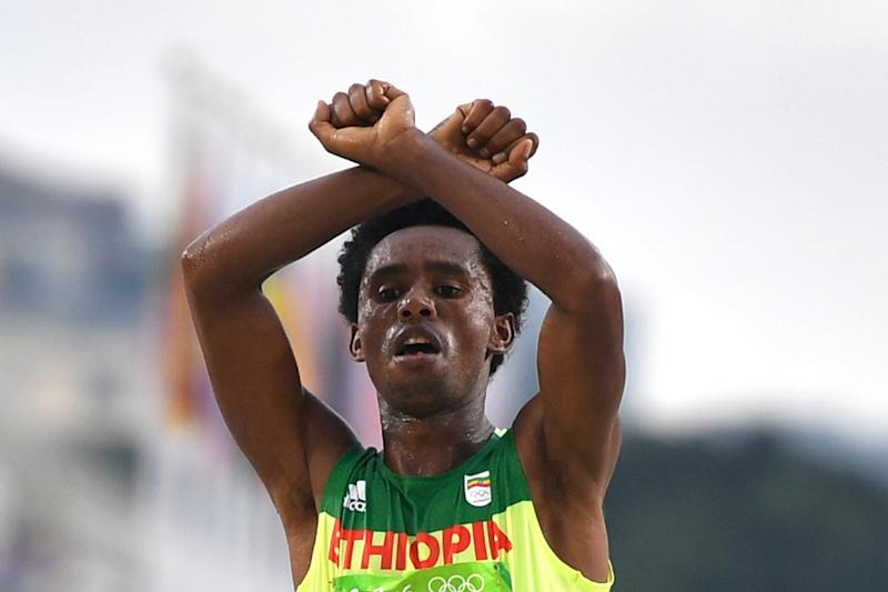 Ethiopia's Feyisa Lilesa crossed his arms above his head at the finish line of the Men's Marathon athletics event of the Rio 2016 Olympic Games (AFP Photo/Olivier Morin)