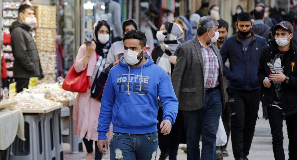 Several people are seen wearing face masks on a street in Iran.