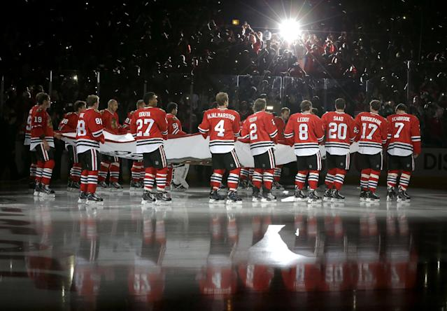 The Chicago Blackhawks carry out the Stanley Cup Championship banner during ceremonies before an NHL hockey game between the Blackhawks and the Washington Capitals Tuesday, Oct. 1, 2013, in Chicago. (AP Photo/Nam Y. Huh)