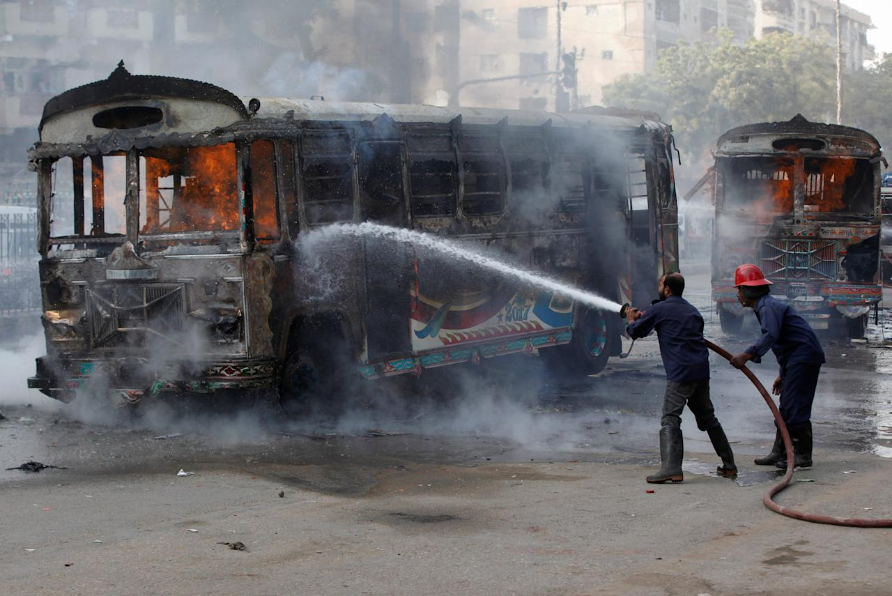 Firefighters douse a fire on buses, which according to local media were set ablaze by people after a girl was killed due to over speeding, along a road in Karachi, Pakistan November 24, 2017. REUTERS/Akhtar Soomro