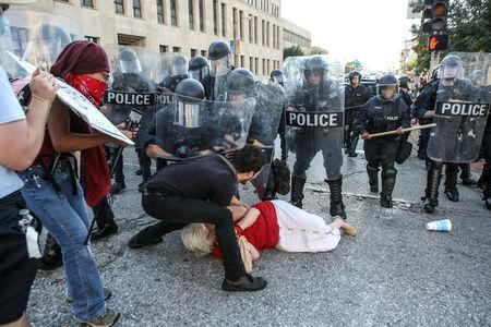 FILE PHOTO: A woman who was pushed down by police is helped by a protester while police try to disperse a crowd, after a not guilty verdict in the murder trial of Jason Stockley, a former St. Louis police officer, charged with the 2011 shooting of  Anthony Lamar Smith, who was black, in St. Louis, Missouri, U.S. on September 15, 2017.   REUTERS/Lawrence Bryant/File Photo
