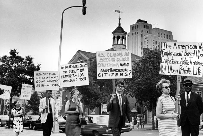 FILE- In this July 4, 1967, file photo, Kay Tobin Lahusen, right, and other demonstrators carry signs calling for protection of homosexuals from discrimination as they march in a picket line in front of Independence Hall in Philadelphia. Lahusen, a pioneering gay rights activist who chronicled the movement's earliest days through her photography and writing died Wednesday, May 26, 2021. She was 91. (AP Photo/John F. Urwiller, File)