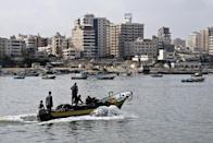 Fishermen ride a small boat into the harbour on August 18, 2014 in Gaza City