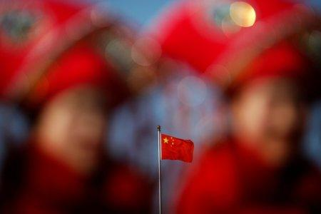 China's national flag is seen behind hostesses waiting for delegates outside the Great Hall of the People during the second plenary session of the National People's Congress (NPC) in Beijing, China March 8, 2017. REUTERS/Damir Sagolj