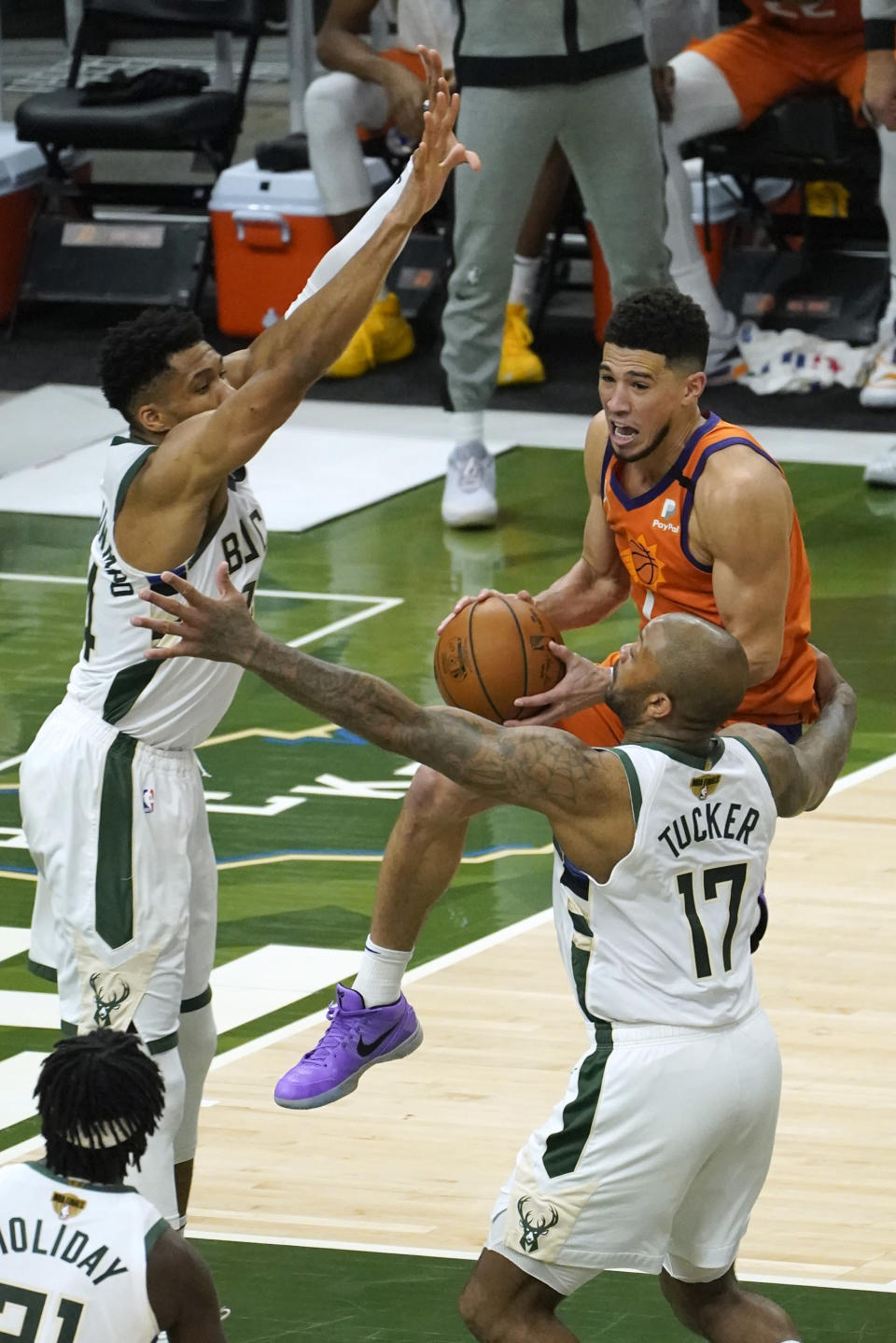 Phoenix Suns guard Devin Booker, center, drives between Milwaukee Bucks forward Giannis Antetokounmpo, left, and forward P.J. Tucker (17) during the second half of Game 4 of basketball's NBA Finals in Milwaukee, Wednesday, July 14, 2021. (AP Photo/Paul Sancya)