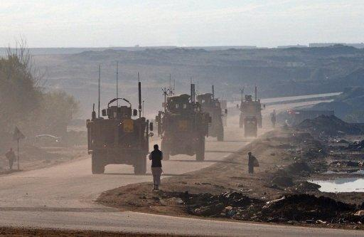 US military vehicles drive along a highway linking Kabul to Bagram, on March 25, 2012.Afghan President Hamid Karzai said Thursday that he could allow the United States to keep nine military bases in the country as part of negotiations over a long-term security pact with Washington
