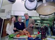 <p>President Clinton, alongside daughter Chelsea and first lady Hillary, pose with their Thanksgiving turkey in the Camp David kitchen, where they spent the holiday in 1995.<i> (Photo: Ho New/Reuters)</i></p>
