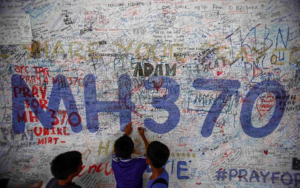 Children write messages for the passengers of MH370 on a wall in Kuala Lumpur airport - Reuters