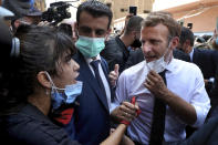 French President Emmanuel Macron, right, speaks with a woman as he visits the Gemayzeh neighborhood, which suffered extensive damage from an explosion on Tuesday that hit the seaport of Beirut, Lebanon, Thursday, Aug. 6, 2020. Macron has arrived in Beirut to offer French support to Lebanon after the deadly port blast. (AP Photo/Bilal Hussein)
