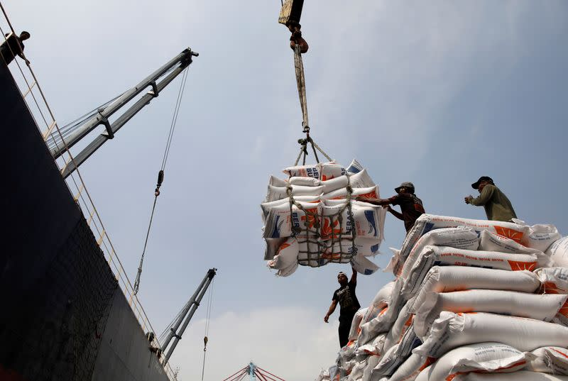 FILE PHOTO: Workers unload bags of rice from a cargo ship onto a truck at Tanjung Priok Port in Jakarta