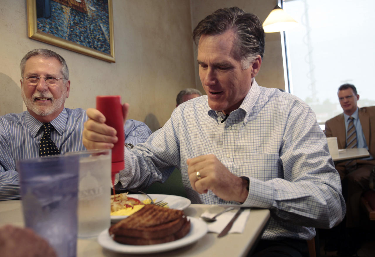 Republican presidential candidate Mitt Romney (R) pours ketchup on his breakfast as he sits next to supporter Peter Ventura during a breakfast stop at the Senate Coney Island restaurant in Livonia, Michigan June 9, 2011. REUTERS/Rebecca Cook   (UNITED STATES - Tags: POLITICS ELECTIONS)