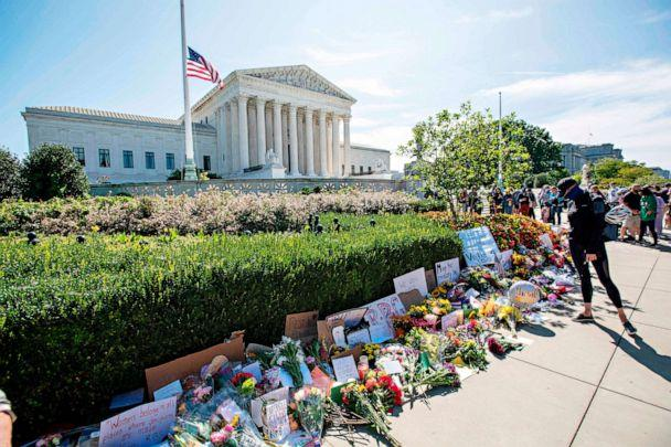 PHOTO: People place flowers outside of the Supreme Court in memory of Associate Justice Ruth Bader Ginsburg, in Washington, on Sept. 19, 2020. (Jose Luis Magana/AFP via Getty Images)