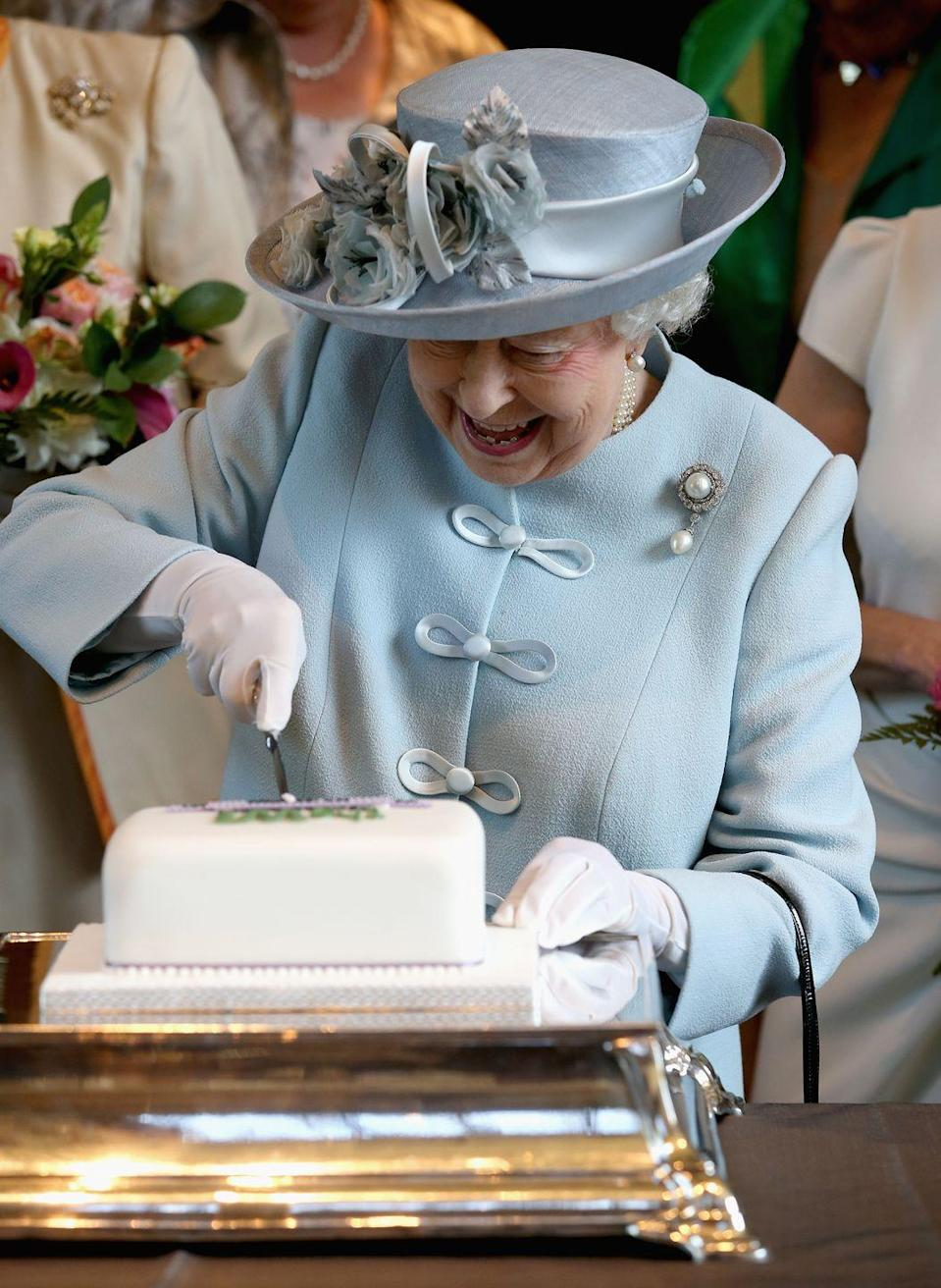 <p>Queen Elizabeth looked delighted cutting into a white cake at the Centenary Annual Meeting of The National Federation Of Women's Institute. </p>