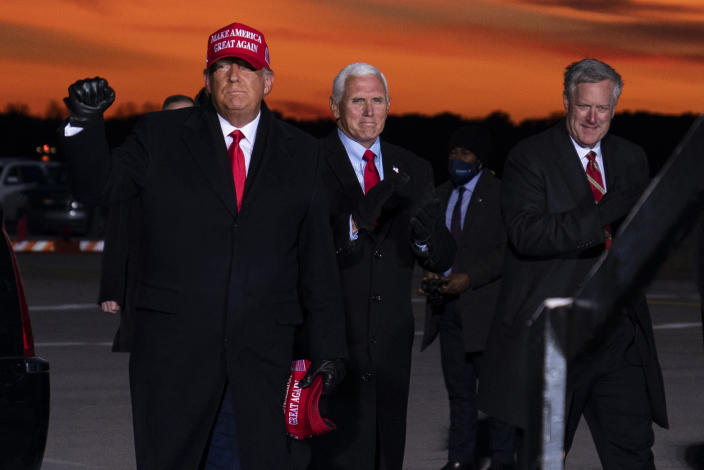 President Donald Trump and Vice President Mike Pence arrive for a campaign rally at Cherry Capital Airport, Monday, Nov. 2, 2020, in Traverse City, Mich., with White House chief of staff Mark Meadows, right. Meadows has been diagnosed with the coronavirus as the nation sets daily records for confirmed cases for the pandemic. (AP Photo/Evan Vucci)