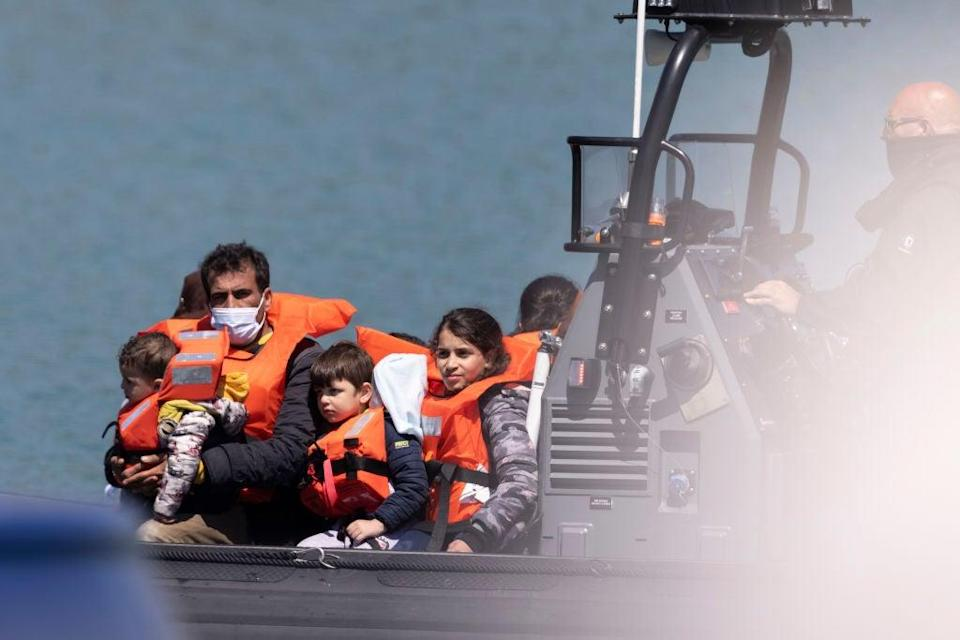 Border Force officials guide newly arrived migrants into port after being picked up in a dinghy in the English Channel on 9 June, 2021 (Getty Images)