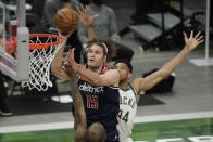 Washington Wizards' Robin Lopez (15) shoots between Milwaukee Bucks' P.J. Tucker and Giannis Antetokounmpo, right, during the first half of an NBA basketball game Wednesday, May 5, 2021, in Milwaukee. (AP Photo/Aaron Gash)