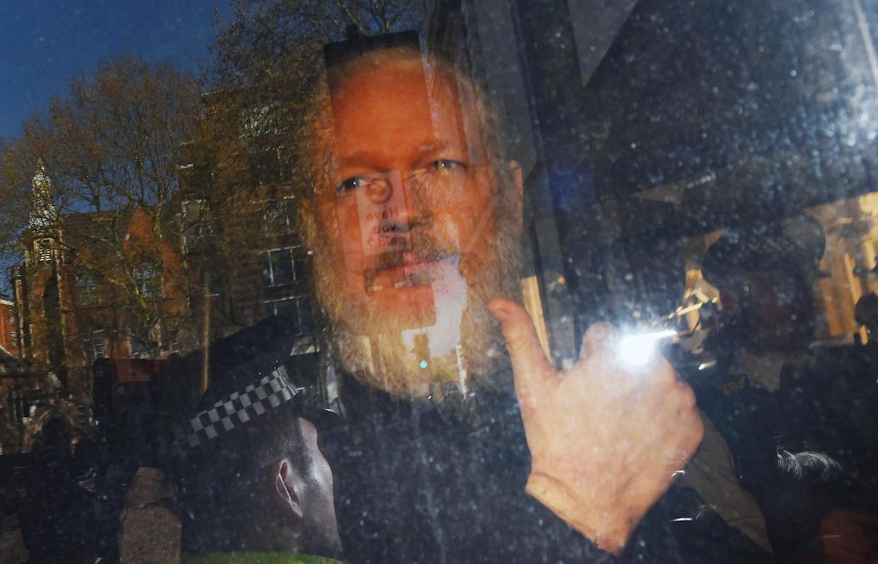 Julian Assange in the back of a police van on Thursday (EPA)
