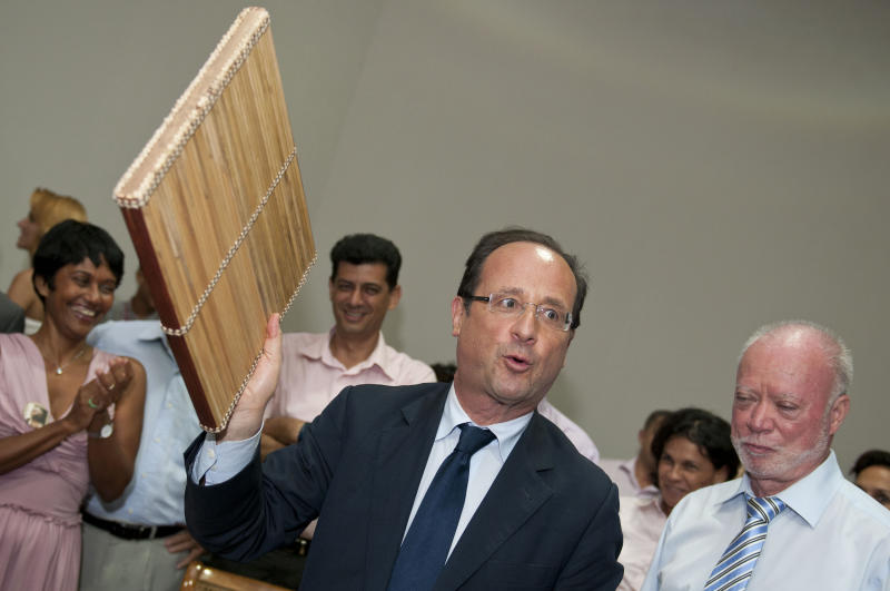 French Socialist party candidate for the presidential elections Francois Hollande, center, holds a Kayam, a local musical instrument, given as a gift as he visits Saint-Benoit, in La Reunion island, Sunday, April 1, 2012. Hollande is on a two-day visit to the French island of the Indian Ocean. (AP Photo/Fabrice Wislez)
