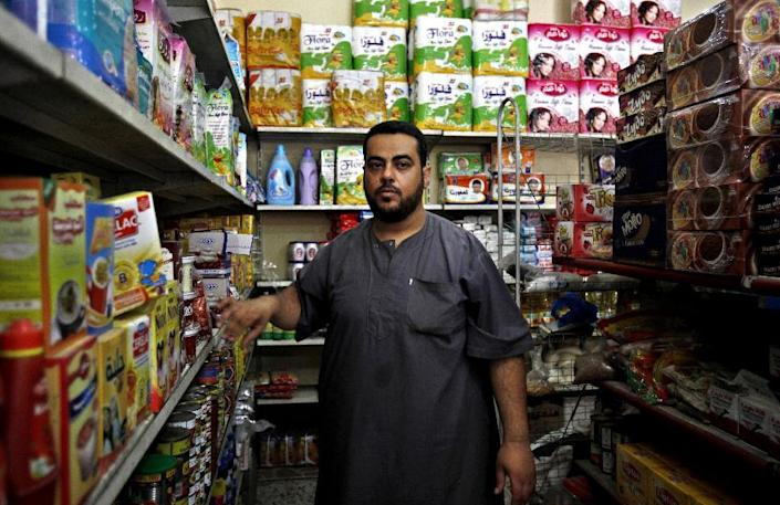 """In this photo taken Wednesday, June 19, 2013. Muhammad Zakout, 38, a Palestinian Muslim Sunni, poses for a photo at his grocery shop at the Shati refugee camp in Gaza City. Hatreds between Shiites and Sunnis are now more virulent than ever in the Arab world because of Syria's brutal civil war. Hard-line clerics and politicians on both sides have added fuel, depicting the fight as essentially a war of survival for their sect. Simply, there is a war against us, the Sunnis. This war is led by Iran and its allies. For me, it's a war against the true Islam and it's a war that serve only the enemies of Islam, like the US and Israel, because they are fighting and dividing countries like Iraq and now Syria and no one fire a single bullet on Israel,"""" Zakout said. (AP Photo/Adel Hana)"""