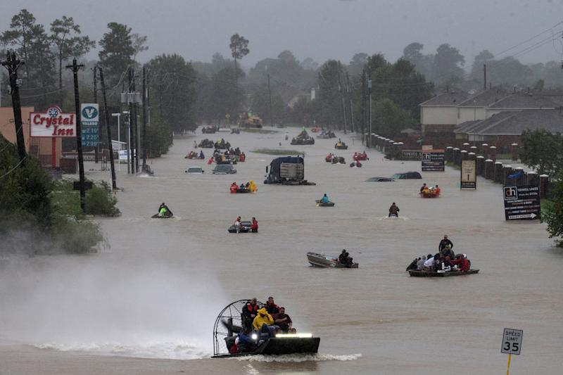 Residents use boats to evacuate flood waters along Tidwell Road east Houston, Texas, on Monday. (Adrees Latif / Reuters)