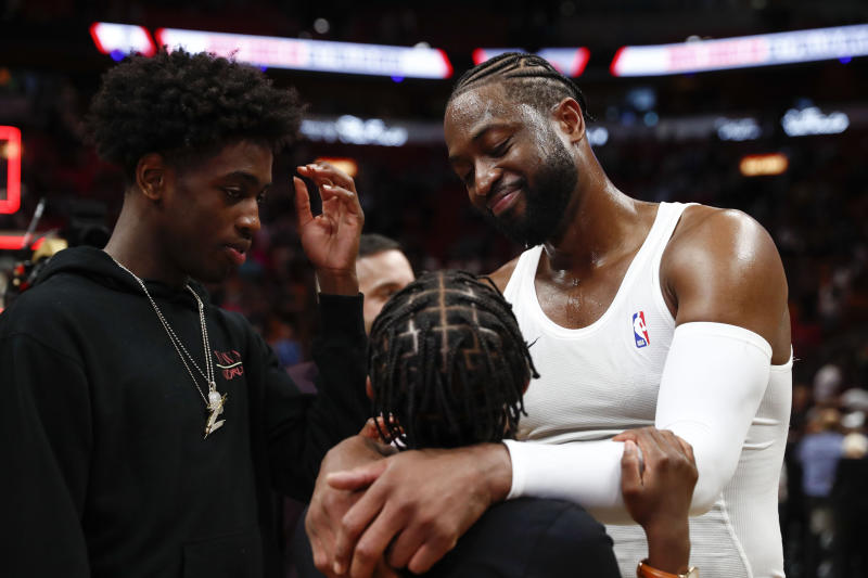 Miami Heat guard Dwyane Wade (3) celebrates with his sons, Zion Wade, right, and Zaire Wade, left after playing in his final NBA basketball game, against the Philadelphia 76ers, Tuesday, April 9, 2019, in Miami. (AP Photo/Brynn Anderson)