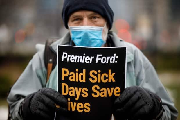 A man holds up a sign during a rally advocating for provincially mandated paid sick days for workers outside Queen's Park in Toronto this January. When Ford took office in 2018, one of his government's first moves was to scrap the Liberals' paid sick days program