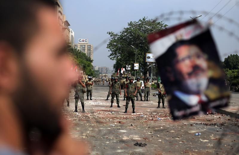 A protester stands next to a poster of ousted President Mohammed Morsi hanged on the barb wire as army soldiers guard at the Republican Guard building in Nasr City, Cairo, Egypt, Tuesday, July 9, 2013. Egyptian security forces killed dozens of supporters of Egypt's ousted president in one of the deadliest single episodes of violence in more than two and a half years of turmoil. The toppled leader's Muslim Brotherhood called for an uprising, accusing troops of gunning down protesters, while the military blamed armed Islamists for provoking its forces. (AP Photo/Khalil Hamra)