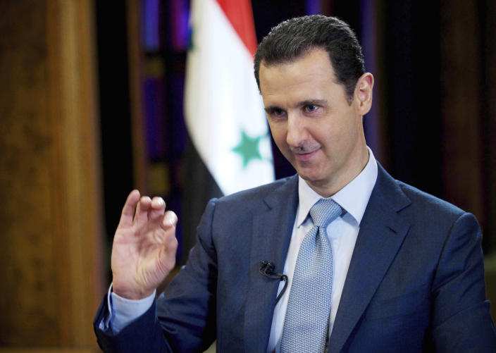 FILE - In this Feb. 10, 2015, file photo released by the Syrian official news agency SANA, Syrian President Bashar Assad gestures during an interview in Damascus, Syria. Assad has snapped up a prize from world powers that have been maneuvering in his country's multifront wars. Without firing a shot, his forces are returning to towns and villages in northeastern Syria where they haven't set foot for years. (SANA via AP, File)