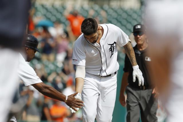 Detroit Tigers third base coach Dave Clark reaches out to designated hitter Nicholas Castellanos as he rounds third on a walk off solo home run during the tenth inning of a baseball game against the Toronto Blue Jays, Sunday, July 21, 2019, in Detroit. (AP Photo/Carlos Osorio)