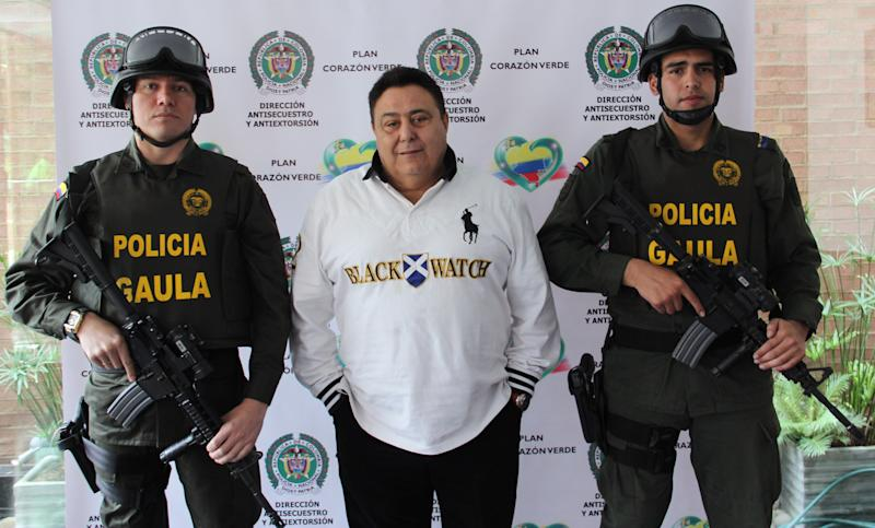 In this photo released by Colombia's National Police, police officers flank alleged Italian drug trafficker Roberto Pannunzi at a police station in Bogota, Colombia, Saturday, July 6, 2013. The fugitive Italian organized crime boss who prosecutors allege arranged monthly shipments of tons of South American cocaine to Europe and was one of the world's most powerful drug brokers, has been captured in Bogota in a shopping mall, Italian and Colombian authorities said Saturday. (AP Photo/Colombia's National Police)