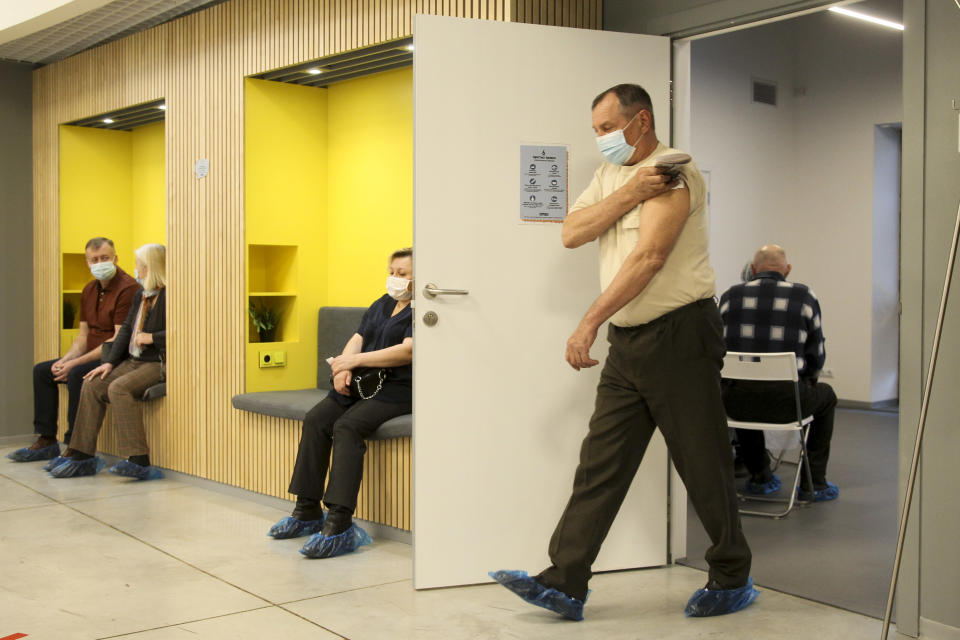 A man wearing a face mask to protect against coronavirus leaves a room after vaccinating with Russia's Sputnik V coronavirus vaccine at a shopping center in Nizhny Novgorod, Russia, Friday, April 2, 2021. Russia has boasted about being the first country in the world to authorize a coronavirus vaccine and rushed to roll it out earlier than other countries, even as large-scale testing necessary to ensure its safety and effectiveness was still ongoing. (AP Photo/Roman Yarovitcyn)