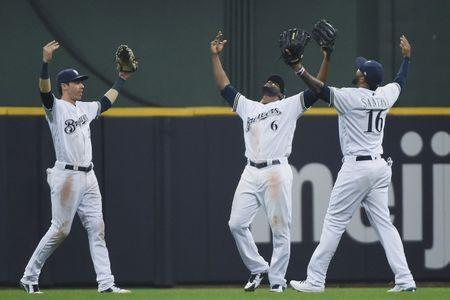 May 21, 2018; Milwaukee, WI, USA; Milwaukee Brewers left fielder Christian Yelich (22), center fielder Lorenzo Cain (6) and right fielder Domingo Santana (16) celebrates after the Brewers defeat the Arizona Diamondbacks at Miller Park. Mandatory Credit: Benny Sieu-USA TODAY Sports