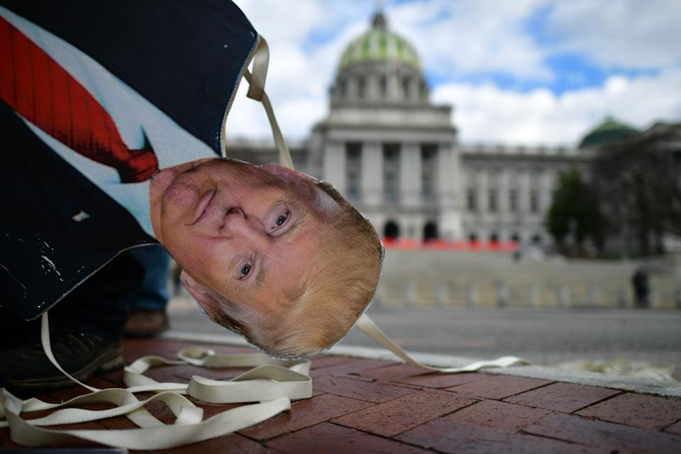 An effigy of President Donald Trump is lowered while people demonstrate against the president outside the Pennsylvania Capitol Building last month. Source: Getty