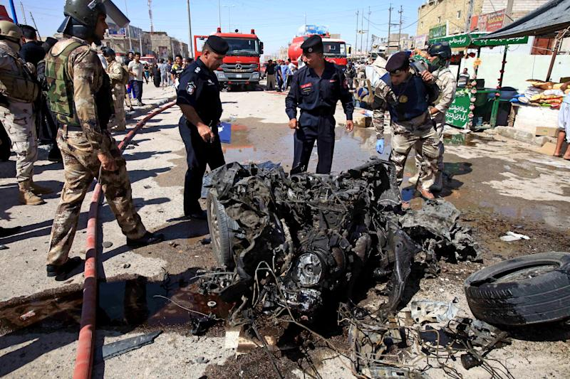 Iraqi security forces inspects wreckage at the site of a car bomb explosion in Basra, 340 miles (550 kilometers) southeast of Baghdad, Iraq, Monday, July 29, 2013. A wave of over a dozen car bombings hit central and southern Iraq during morning rush hour on Monday, officials said, killing scores in the latest coordinated attack by insurgents determined to undermine the government. (AP Photo/Nabil al-Jurani)