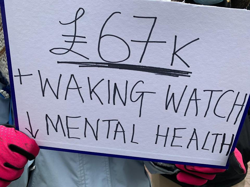 A sign held by a protester, protesting against the cost of waking watches - it says '£67k + Waking Watch - Mental Health'