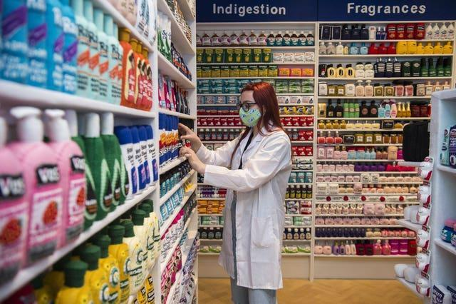 Gallery assistant Scarlett Taulbut organises shelves in artist Lucy Sparrow's NHS themed felt chemist art installation (Kirsty O'Connor/PA)