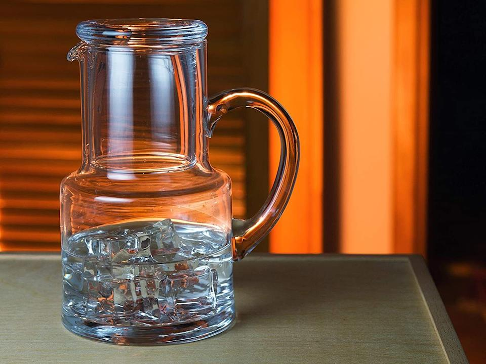"""Soyou can quench that middle-of-the-night thirst without having to make that dreadful walk to the fridge.<br /><br /><strong>Promising review:</strong>""""My wife often gets up in the middle of the night for water and she wanted something close by and not have to go to the refrigerator. This carafe is absolutely perfect for her. First, it is very high quality, exquisitely made, and holds just the right amount of water/ice for keeping on the nightstand overnight. For all day, you'd want an insulated tumbler perhaps, but she fills this halfway with ice cubes and fills enough water just to the neck. it stays cold all night. Any leftover water, she just waters her plants with. My wife and I both have difficulty lifting some objects, but this glass carafe, though solid and substantial, has a very big glass handle so it is easy for her to pour water into the included cup and cover. It came quite fast, extremely well-packed to prevent breakage, and should serve her well for many years."""" — <a href=""""https://www.amazon.com/gp/customer-reviews/RDCLWVQ9DMZC4?&linkCode=ll2&tag=huffpost-bfsyndication-20&linkId=e15f91a31aec813aa01d973b0736be89&language=en_US&ref_=as_li_ss_tl"""" target=""""_blank"""" rel=""""noopener noreferrer"""">Bob Foss</a><br /><br /><strong><a href=""""https://www.amazon.com/dp/B075Y4YJ2S?&linkCode=ll1&tag=huffpost-bfsyndication-20&linkId=baf15351ee25215f4642984eb9497dae&language=en_US&ref_=as_li_ss_tl"""" target=""""_blank"""" rel=""""noopener noreferrer"""">Get it from Amazon for $44.95.</a></strong>"""