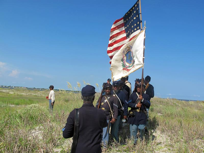 """A color guard of re-enactors marches back after a wreath was placed on a dune on Morris Island near Charleston, S.C., on Thursday, July 18, 2013. The wreath commemorated the fallen on the 150th anniversary of the charge of the black 54th Massachusetts Volunteer Infantry in a fight commemorated in the film """"Glory."""" (AP Photo/Bruce Smith)"""