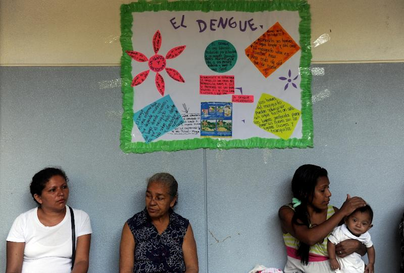 People sitting under a poster providing information about dengue fever, wait for medical attention at a health centre in Managua, on October 8, 2009