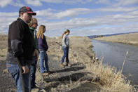 FILE - In this March 2, 2020, file photo, farmer Ben DuVal with his wife, Erika, and their daughters, Hannah, third from left, and Helena, fourth from left, stand near a canal for collecting run-off water near their property in Tulelake, Calif. Federal officials announced Wednesday that farmers who rely on a massive irrigation project spanning the Oregon-California border will get 8% of the deliveries they need amid a severe drought. (AP Photo/Gillian Flaccus, File)