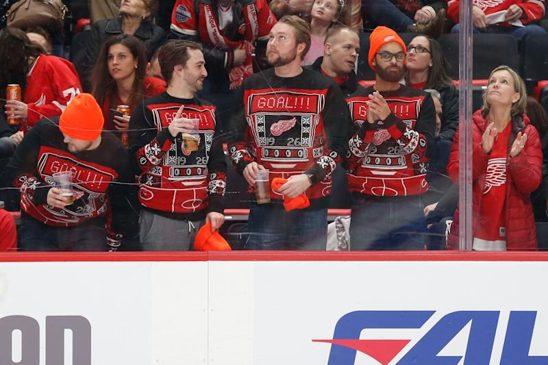 Detroit fans wearing matching Red Wing-themed ugly Christmas sweaters at a game on Dec. 22, 2018. (Photo: Icon Sportswire via Getty Images)