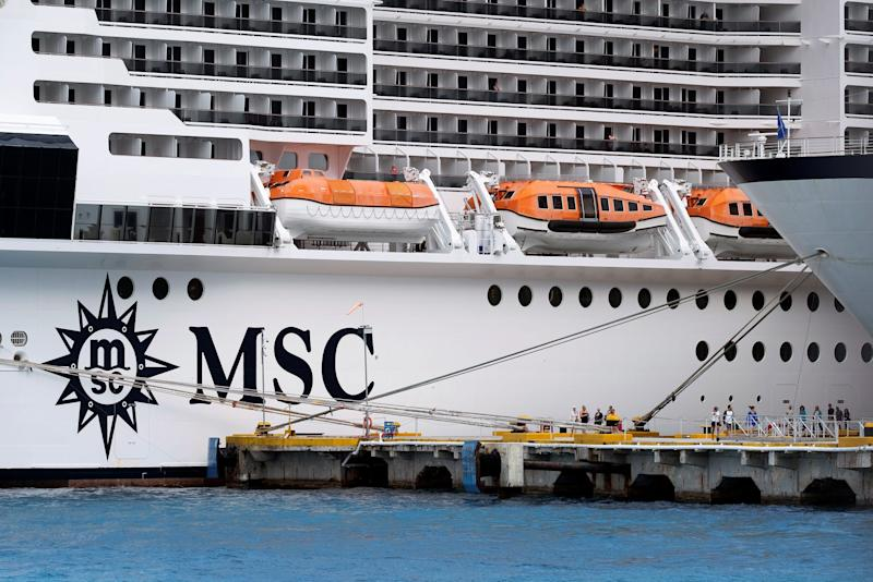 12 Tourists stand next to Cruise liner MSC Meraviglia, berthed at a dock in Punta Langosta, in Cozumel