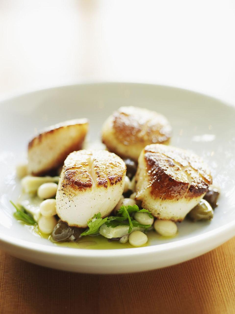 """<p>A <a href=""""https://www.seafoodhealthfacts.org/seafood-choices/description-top-commercial-seafood-items/scallops"""" rel=""""nofollow noopener"""" target=""""_blank"""" data-ylk=""""slk:3-oz. serving of steamed scallops"""" class=""""link rapid-noclick-resp"""">3-oz. serving of steamed scallops</a> has 17 grams of protein for just 90 calories. That much protein will keep you full till your next meal. </p><p><strong>Recipe to try:</strong> <a href=""""https://www.womansday.com/food-recipes/food-drinks/recipes/a31935/bacon-wrapped-scallops-recipe-ghk0810/"""" rel=""""nofollow noopener"""" target=""""_blank"""" data-ylk=""""slk:Bacon-Wrapped Scallops"""" class=""""link rapid-noclick-resp"""">Bacon-Wrapped Scallops</a></p>"""